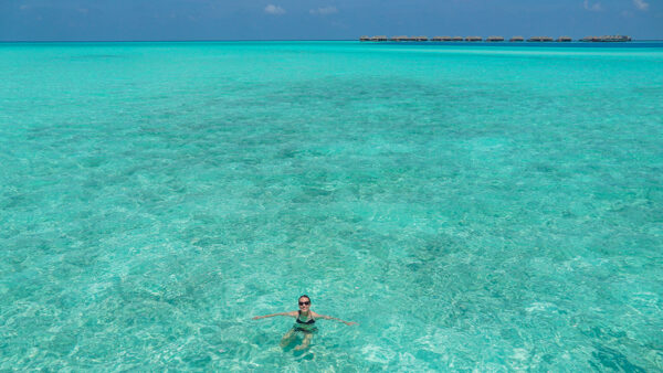 Swimming in the Indian Ocean with Overwater Bungalows in Background